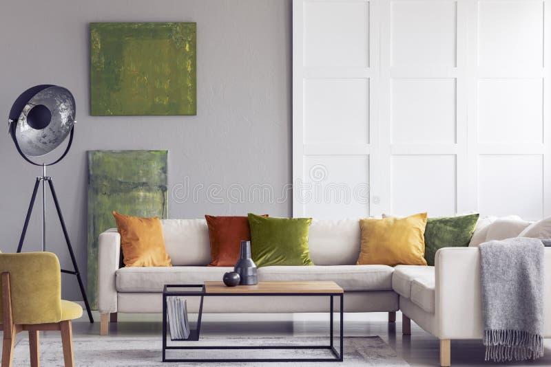 Gele en groene hoofdkussens op witte sofa in woonkamerbinnenland met schilderijen en lamp Echte foto royalty-vrije stock afbeeldingen