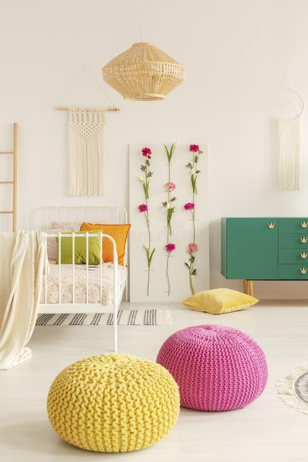 Gele en roze poef in het midden van boho vrouwelijke slaapkamer met groen kabinet, bloemraad, eenpersoonsbed en macramé op de muu royalty-vrije stock foto's