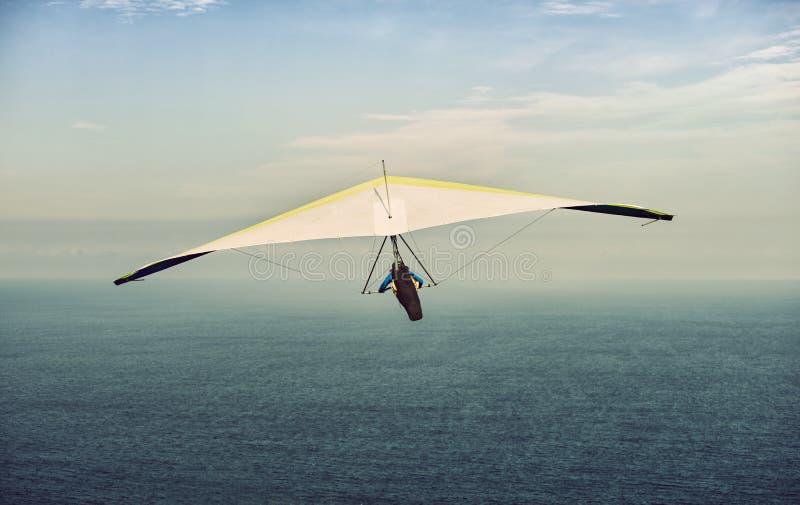 Gele en witte deltavlieger tijdens de vlucht weg met wolkenhemel stock afbeeldingen