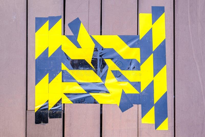 Gele en zwarte voorzichtigheidsband duidelijk op gebroken houten vloer royalty-vrije stock fotografie