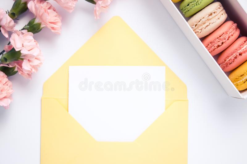 Gele envelop met document voor tekst en mooie anjerbloemen met makarons Ge?soleerde royalty-vrije stock foto's
