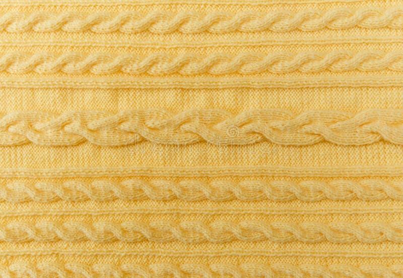 Gele Gebreide Achtergrond met Patroon en Vlechten Gemaakte hand - stock afbeelding