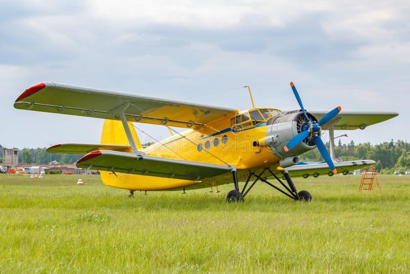 Gele geschilderde legendarische sovjetdievliegtuigentweedekker Antonov een-2 op een groen gras van vliegveld tegen bewolkte hemel stock foto's