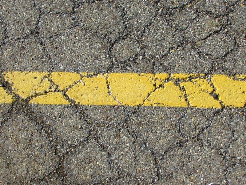 Gele, geschilderde lijn op gebarsten weg royalty-vrije stock fotografie