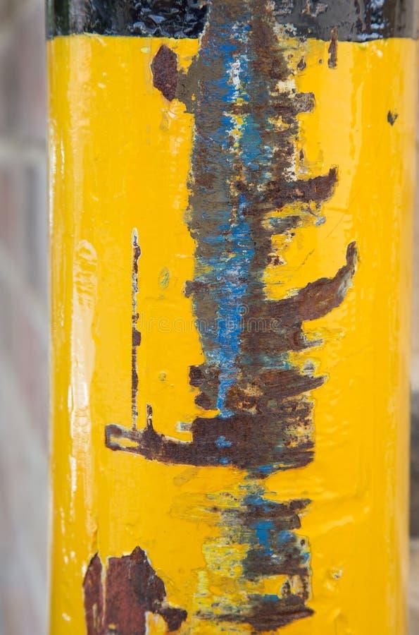 Gele geschilderde post met de abstracte textuur van de voertuigschade stock afbeelding