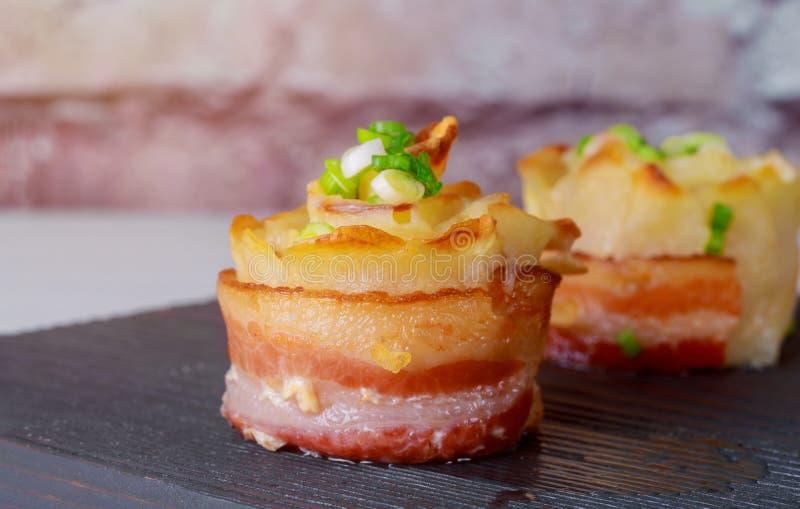 Gele gesneden die aardappels met bacon in de oven wordt gekookt stock afbeeldingen