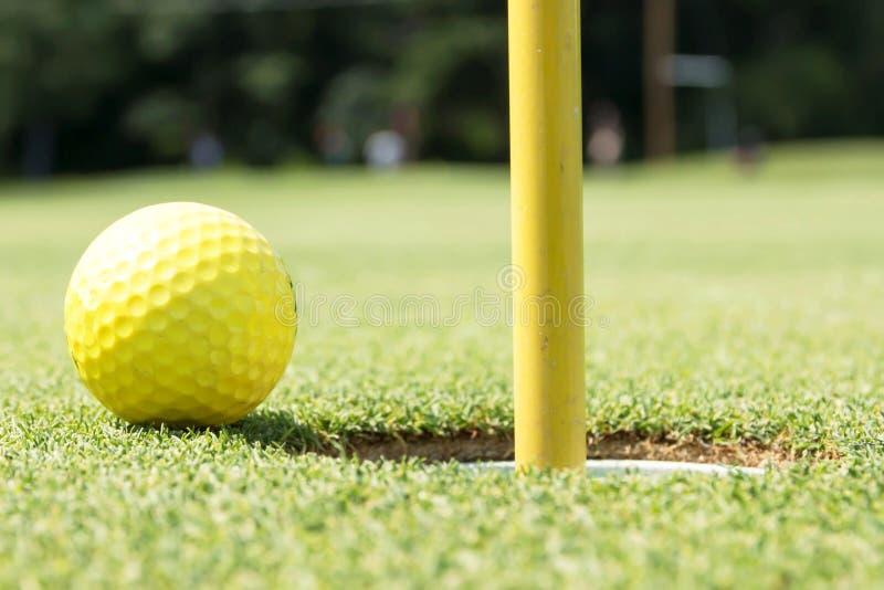 Gele golfbal op rand van gat stock afbeeldingen
