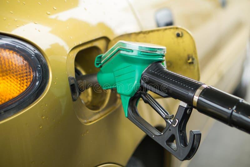 Gele, gouden auto bij een benzinestation die met brandstof worden gevuld stock afbeeldingen