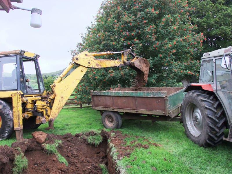 Gele Graaf gravende stichtingen voor een uitsterven aan een bungalow met tractor en aanhangwagen royalty-vrije stock fotografie