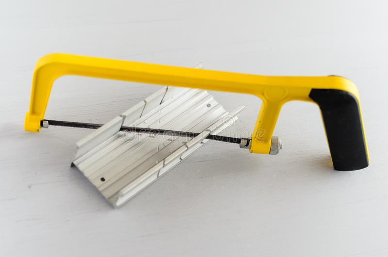 Gele handzaag en aluminiummijterdoos voor hobby in huisworkshop royalty-vrije stock foto