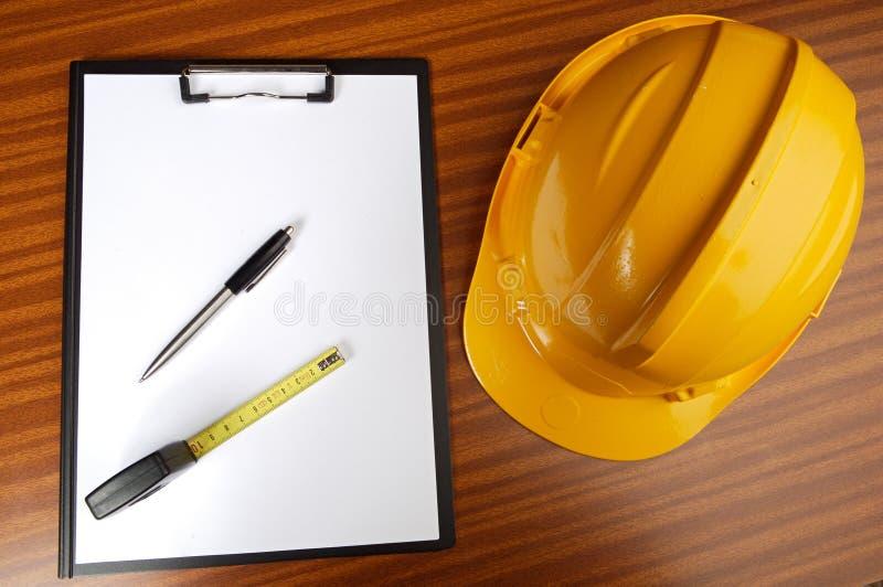 Gele helm en blocnote royalty-vrije stock afbeeldingen