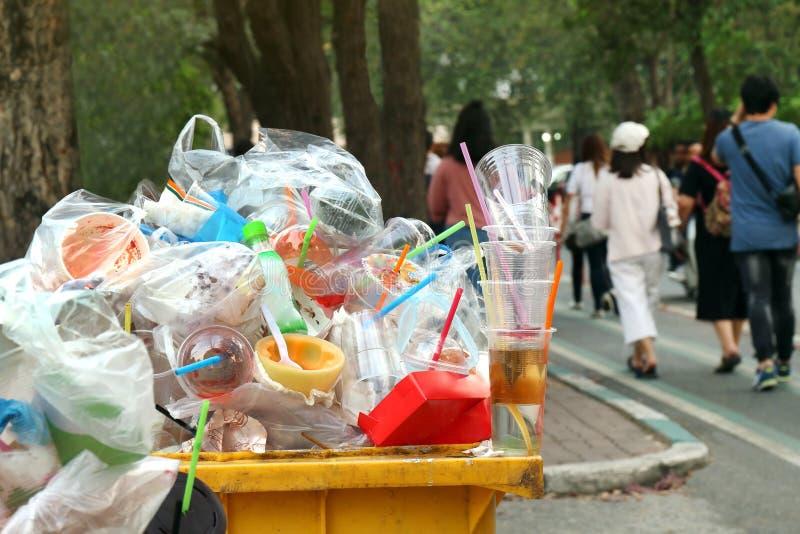 Gele het afvalhoogtepunt van het huisvuil lopen het plastic Afval van afvalbak en de achtergrondmensen op de stoeptuin, Huisvuilb stock fotografie