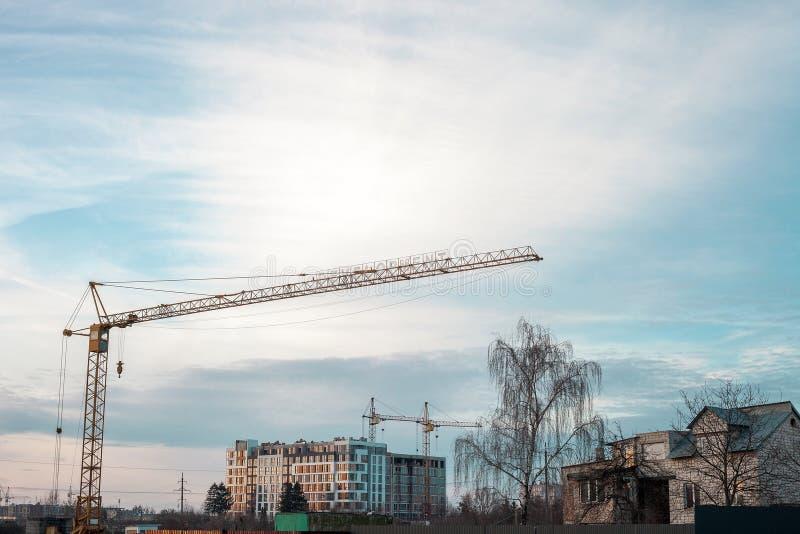 Gele hoge torenkranen die huis bouwen bij zonsondergang royalty-vrije stock foto