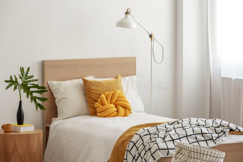 Gele hoofdkussens en comfortabele deken op eenpersoonsbed in elegante hotelruimte, groen blad in zwarte vaas op houten bedlijst stock afbeeldingen