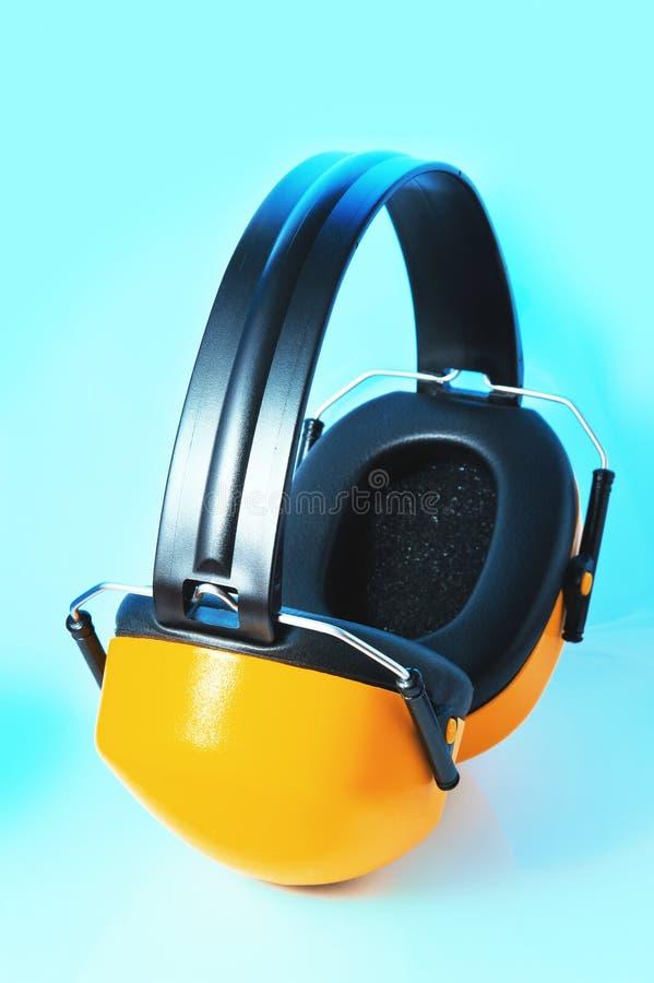 Gele hoofdtelefoons tegen lawaai op blauwe achtergrond royalty-vrije stock fotografie