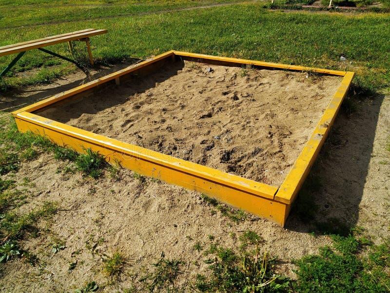 Gele houtconstructie met zand op de groene Speelplaats voor jonge geitjes Status naast de bank stock fotografie