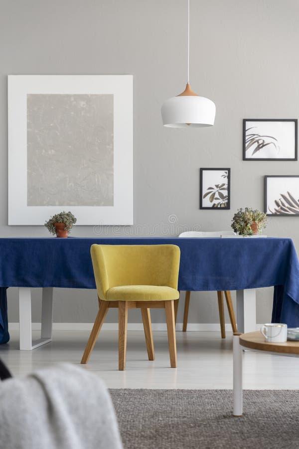 Gele houten stoel bij lijst met blauwe doek in modern eetkamerbinnenland met model royalty-vrije stock afbeeldingen