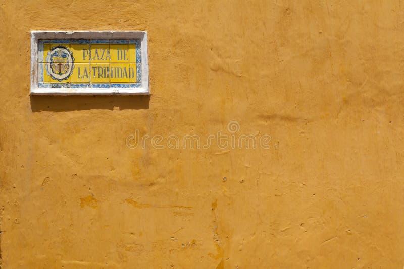 Gele huismuur met betegeld straatteken stock foto's