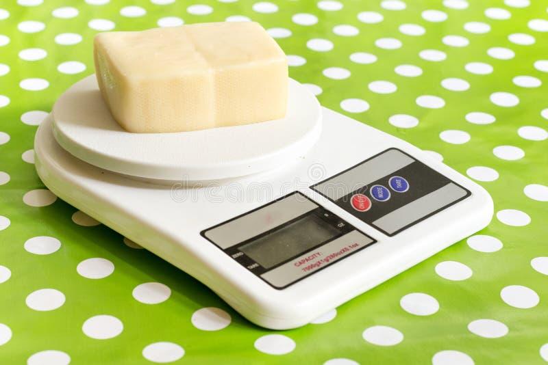 Gele kaas op de keuken digitale schaal stock afbeeldingen
