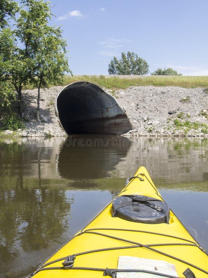 Gele kajak op rivier die naar de tunnel gaan stock afbeeldingen