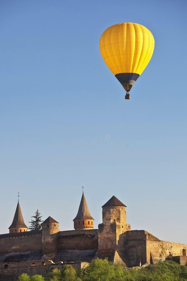 Gele kleurrijke hete luchtballon die in blauwe hemel over daken van stad vliegen royalty-vrije stock fotografie