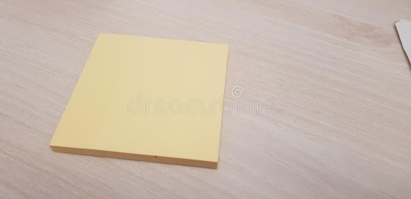 Gele kleverige nota zonder tekst die op een lichte houten achtergrond moet worden gevuld stock afbeeldingen