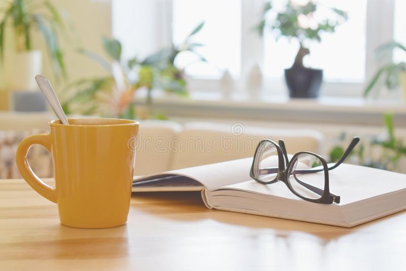 Gele kop thee, boek en glazen op de lijst, comfortabele huis binnenlandse achtergrond stock foto's