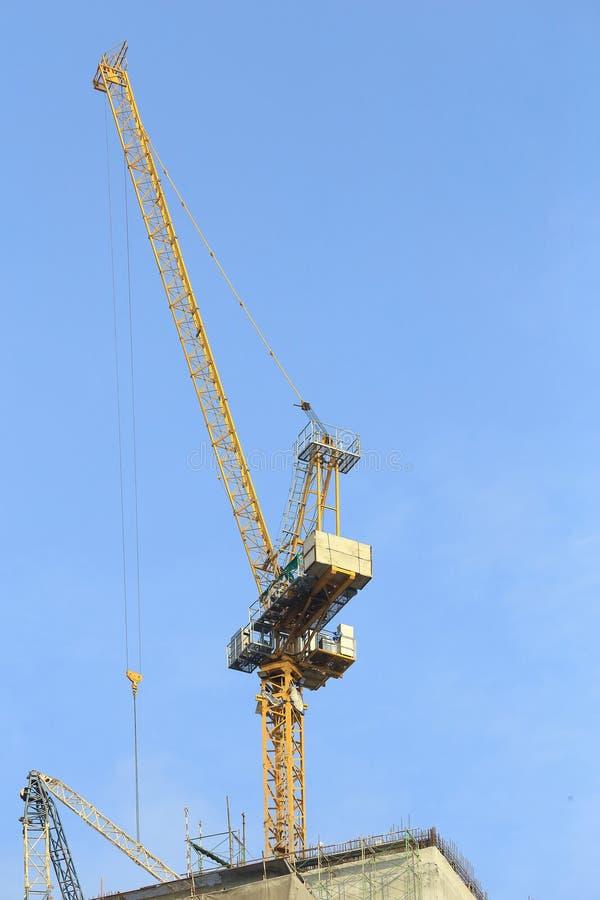 Gele kranen in bouwwerf met blauwe hemel stock foto