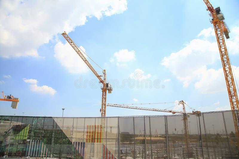 Gele kranen in bouwwerf met blauwe hemel en wolk, als architectuurachtergrond royalty-vrije stock afbeeldingen