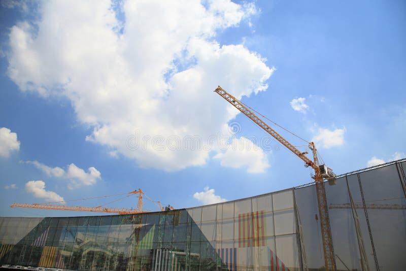 Gele kranen in bouwwerf met blauwe hemel en wolk, als architectuurachtergrond stock afbeelding