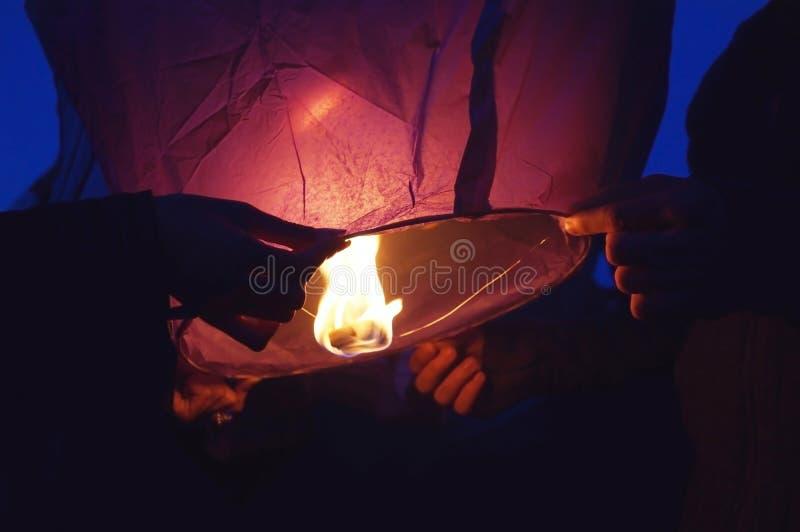 Gele lantaarn in menselijke handen op donkere achtergrond stock afbeelding