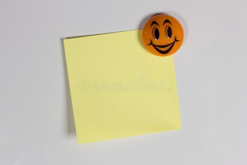 Gele lege sticker op de koelkast met een vrolijke glimlachkoelkast royalty-vrije stock afbeelding
