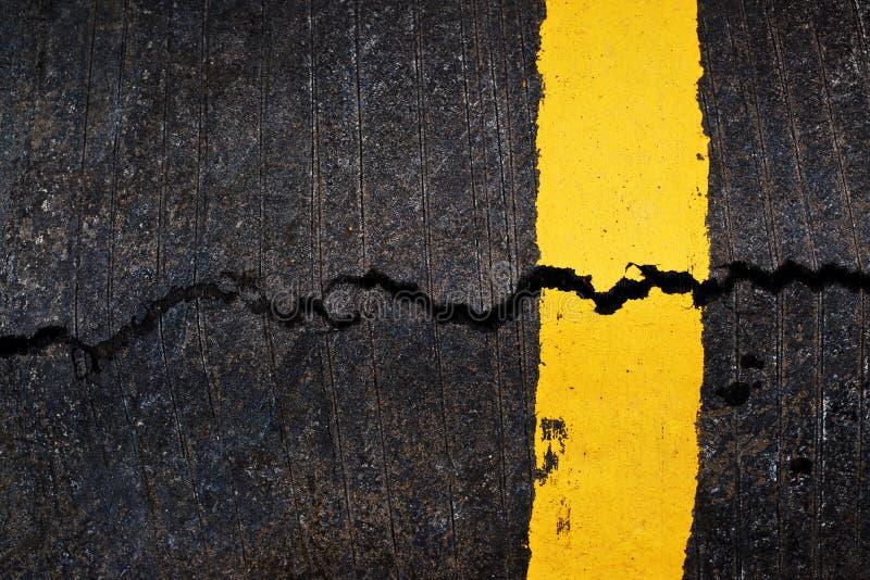 Gele lijn op gebarsten asfaltweg stock fotografie