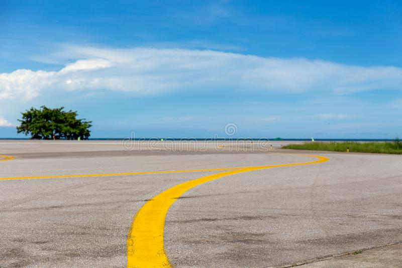Gele lijn op taxibaan bij vliegveld met overzees en blauwe hemelbackgro royalty-vrije stock afbeelding