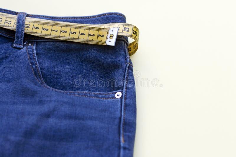 Gele maatregelenband in jeans op achtergrond, concept gewichtsverlies, exemplaarruimte stock foto