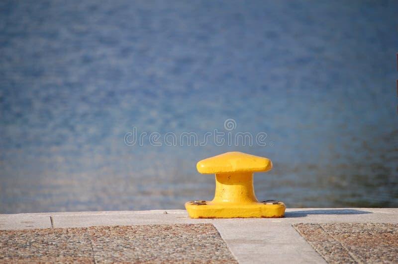 Gele meerpaal op pijler met overzeese mening stock afbeelding