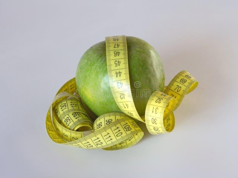 Gele metende band die rond een heerlijke groene appel wordt verpakt stock foto