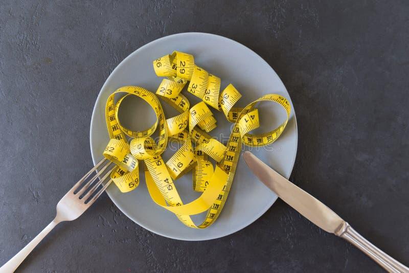 Gele metende band op plaat, vork met mes op donkere achtergrond stock afbeeldingen