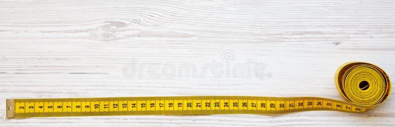 Gele metende band op witte houten lijst, hoogste mening Van hierboven, vlak leg stock foto
