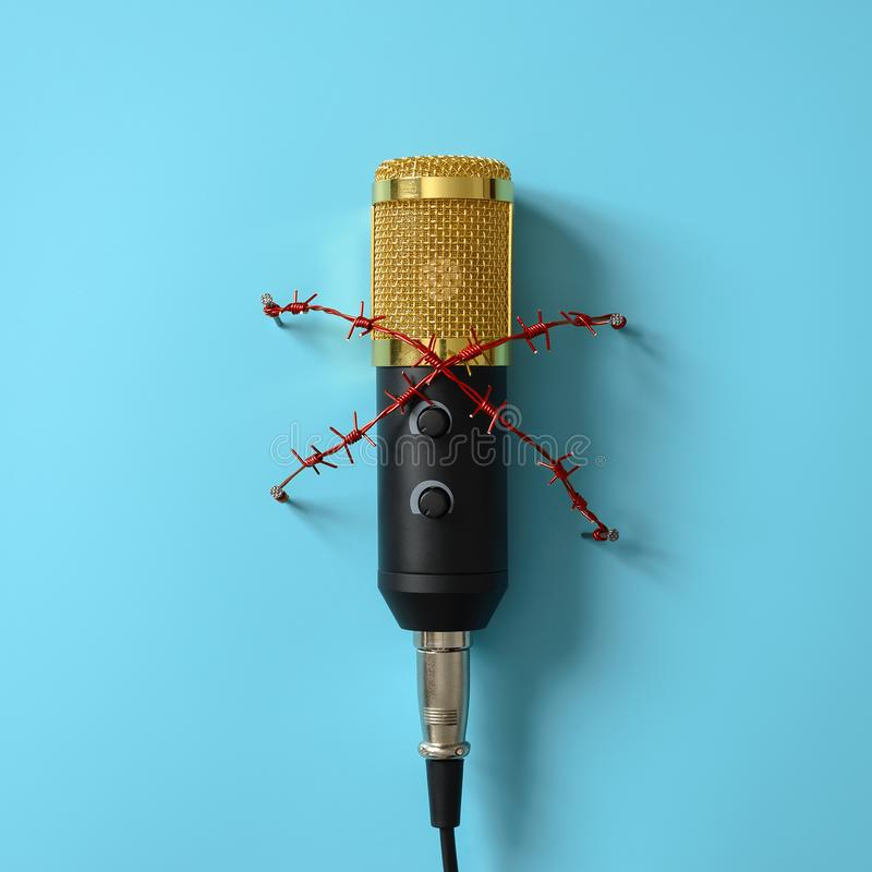 Gele microfoon met rood prikkeldraad Concept op het gebied van censuur of persvrijheid stock foto