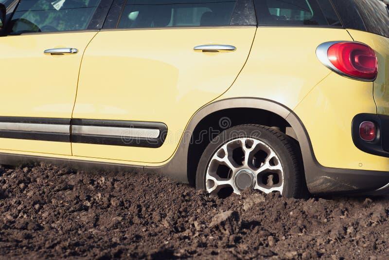 Gele moderne die SUV-auto in de modder wordt geplakt Gebroken voertuig royalty-vrije stock foto's
