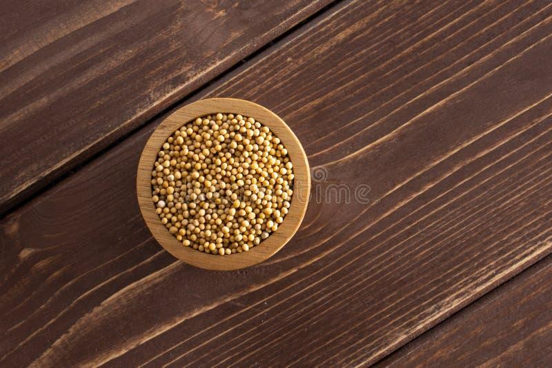 Gele mosterdzaden op bruin hout royalty-vrije stock afbeeldingen
