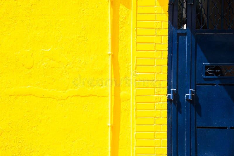 Gele muur en blauwe metaaldeur royalty-vrije stock foto's