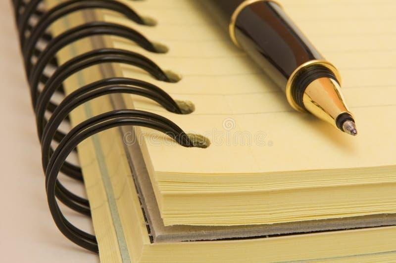 Gele notitieboekje en pen royalty-vrije stock foto