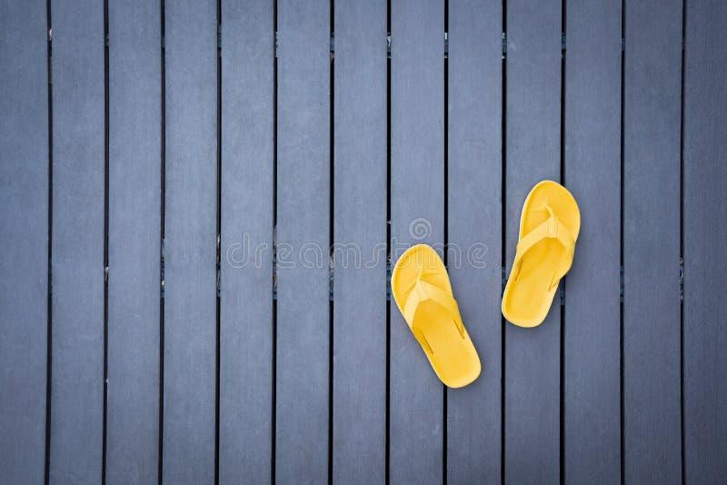 Gele pantoffels op donkere houten latjesvloer royalty-vrije stock foto