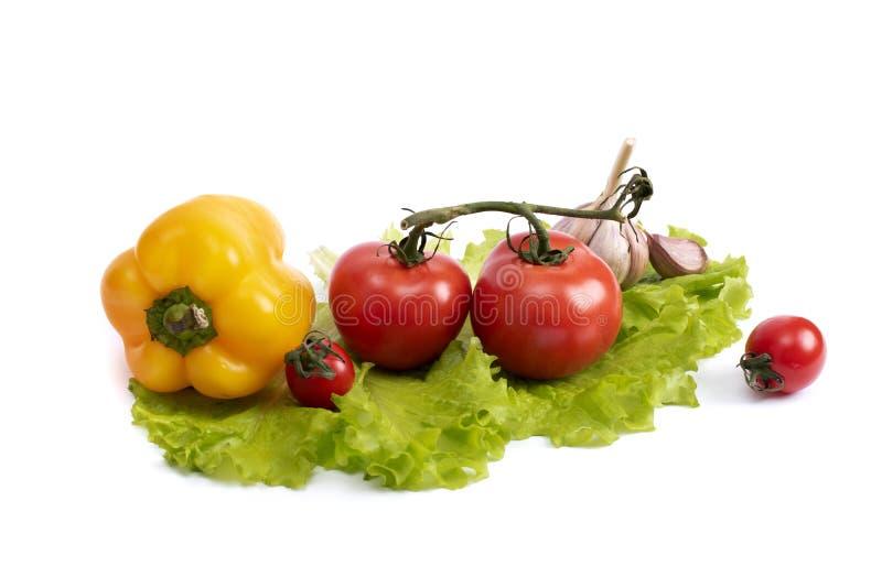 Gele paprika en rode tomaten op een blad van groene salade Gele peper en tomaten op een wit geïsoleerde achtergrond royalty-vrije stock afbeelding