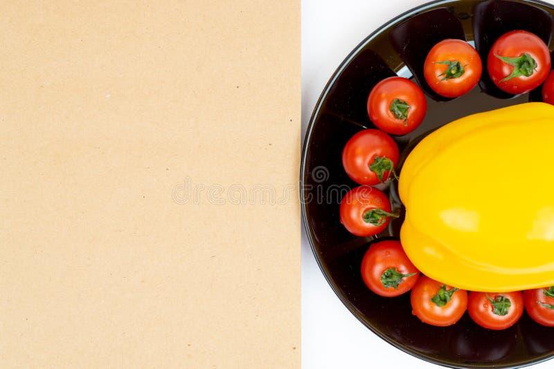 Gele paprika met tomaten in een zwarte plaat die op witte achtergrond dichtbij Blocnote wordt geïsoleerd Samenstelling van geel p royalty-vrije stock fotografie