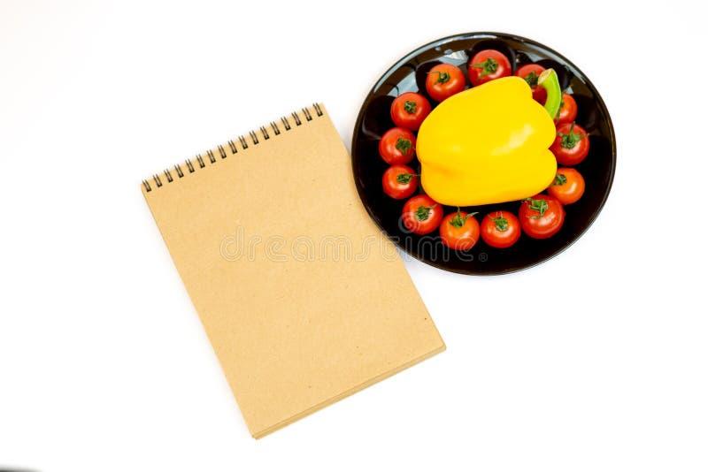 Gele paprika met tomaten in een zwarte plaat die op witte achtergrond dichtbij Blocnote wordt ge?soleerd Samenstelling van geel p stock afbeelding