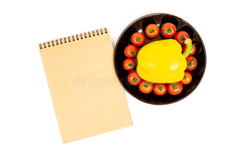 Gele paprika met tomaten in een zwarte plaat die op witte achtergrond dichtbij Blocnote wordt ge?soleerd Samenstelling van geel p stock foto