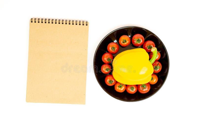 Gele paprika met tomaten in een zwarte plaat die op witte achtergrond dichtbij Blocnote wordt ge?soleerd Samenstelling van geel p royalty-vrije stock afbeeldingen